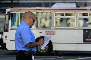 Muni street inspector Marcus Marcic logs the arrival time of an inbound bus at the corner of Van Ness Avenue and Market Street in San Francisco, Calif. on Friday, Sept. 7, 2012. Photo: Paul Chinn, The Chronicle / SF